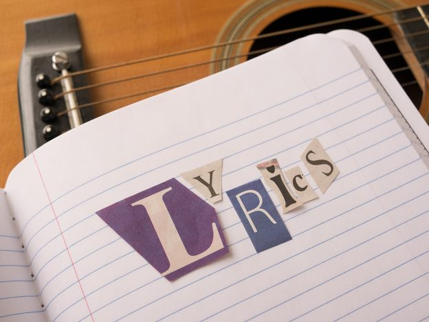Cut out letters placed on a notebook spell lyrics